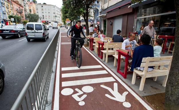 Una terraza hostelera linda con el carril bici en la calle de Casimiro Sainz. Los ciclistas están protegidos de los coches por una barandilla.